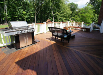 grand ipe deck with king posts and white vinyl rails deck specialists inc